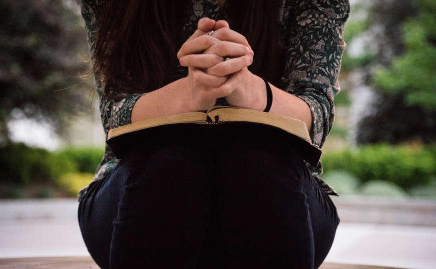 Mujer orando con biblia en mano