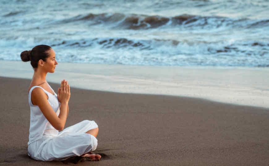 salud abundante mujer meditando en la playa